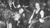 """L7's Jennifer Finch playing live to a rowdy crowd on the back cover of the 'Shove' 7"""" single"""
