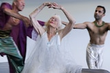 103-year-old Eileen Kramer in a glittering silver dress dances while sitting with two male dancers in the background