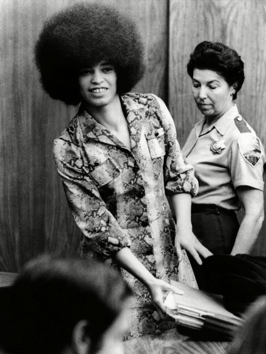 A black and white 70s photo of a Black woman with an afro, Angela Davis, she gathers documents as a white court officer looks on