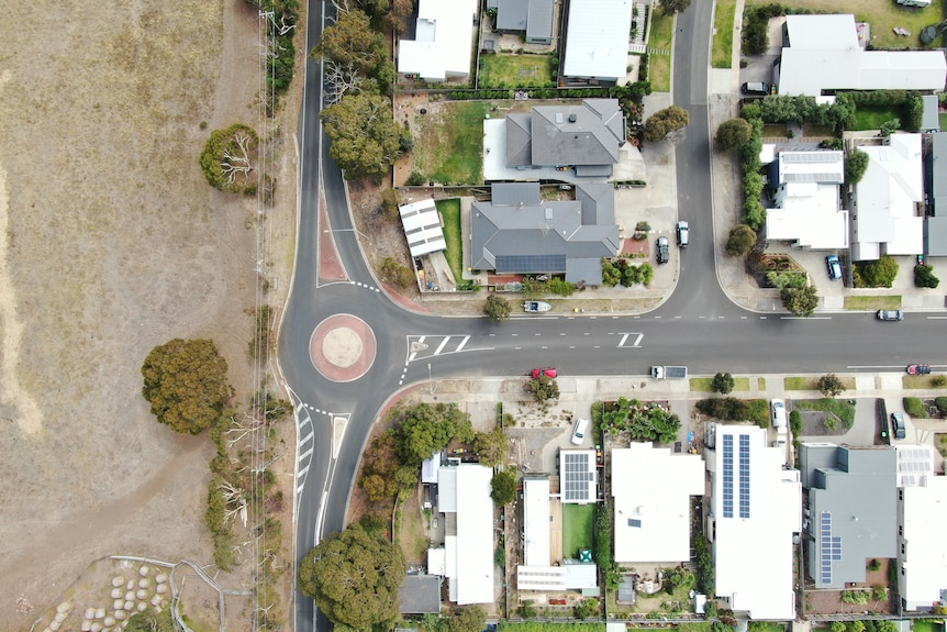 An aerialbirdseye view shot showing a road separating housing and a piece of undeveloped land.