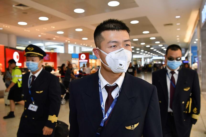 Three male flight crew wear masks as they walk through Sydney airport