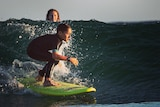 Young boy on a surfboard riding the waves