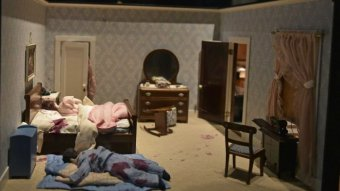 A doll house-style miniature bedroom splattered with blood. A blood covered doll lies on the floor.