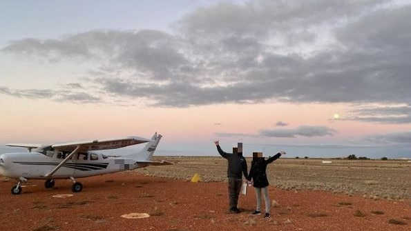 Two people next to a small plane on red dirt