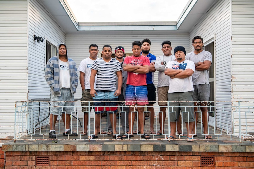 Nine Samoan men stand outside their home in Inverell, with serious expressions on their faces. Five cross their arms.