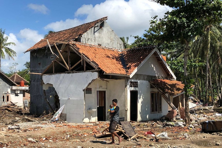A man wearing a black shirt holds a baby as he walks past a wrecked house.