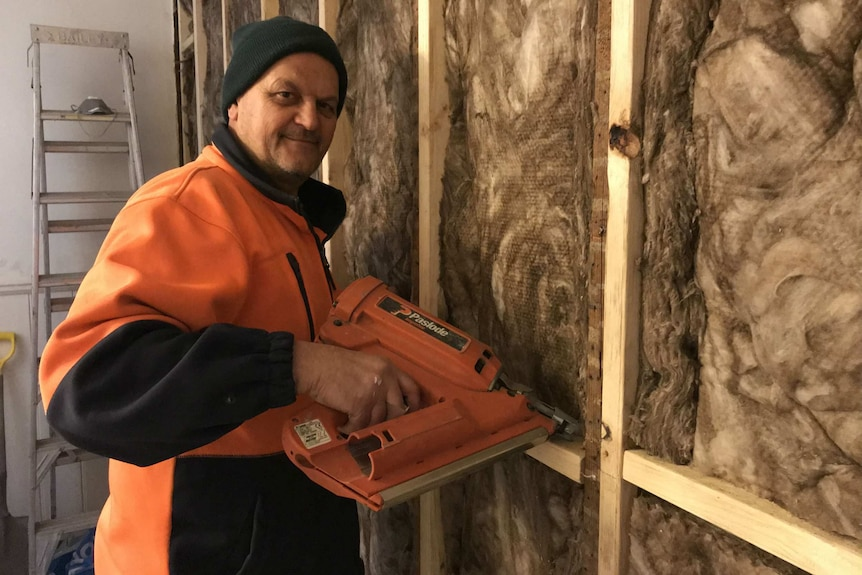 John Najjar holds a nail gun while working to renovate a house, he survived a serious financial collapse/crisis.