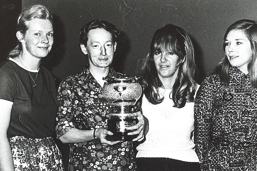 Black-and-white photograph of four smiling women, with one holding a trophy.