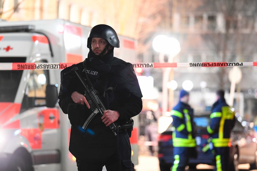 A police officer dressed entirely in black holds a large automatic weapon. An ambulance is behind him.