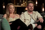 A man and a woman sit next to each other on a confessional couch on a reality show. The woman looks unhappy as the man talks.