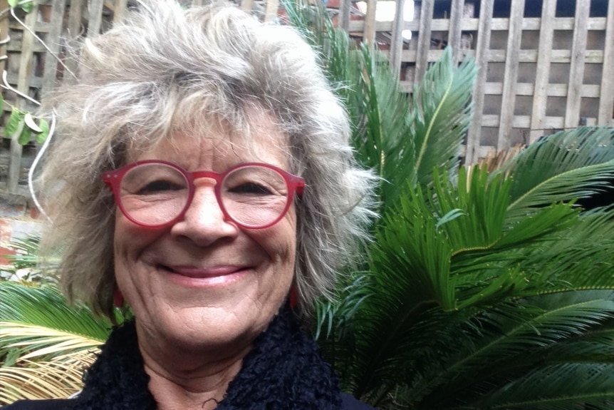 Dr Green is smiling. She has grey hair and red-framed glasses and there is a big green plant behind her.
