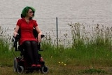 A woman in her wheelchair on the side of the road in the countryside