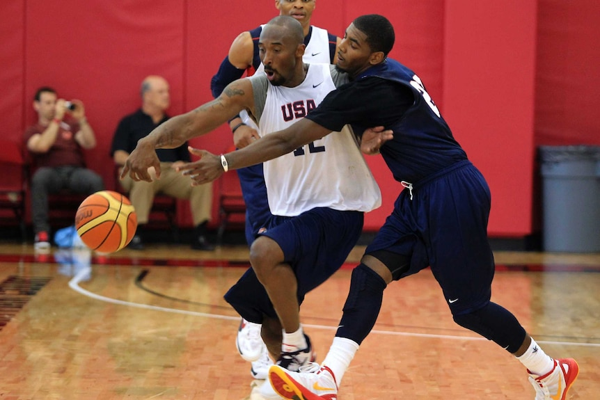 Kyrie Irving stretches across Kobe Bryant to try to take the ball off him.