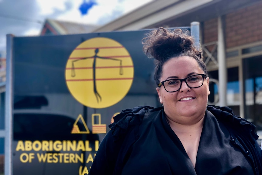 Geraldton Aboriginal Legal Service managing lawyer Kate Turtley-Chappel standing in front of a black sign.