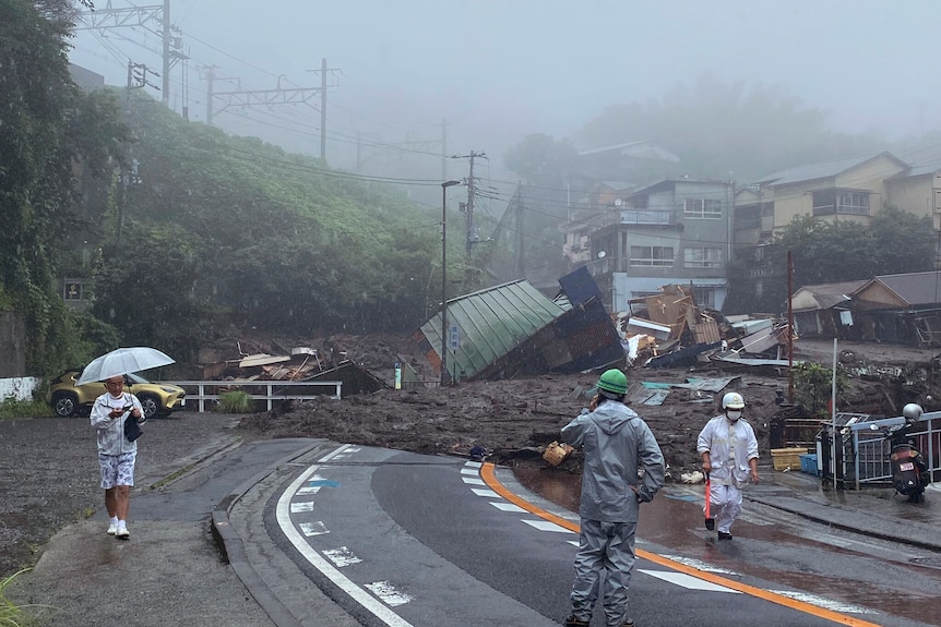 A road is covered by mud and debris following a mudslide and heavy rain