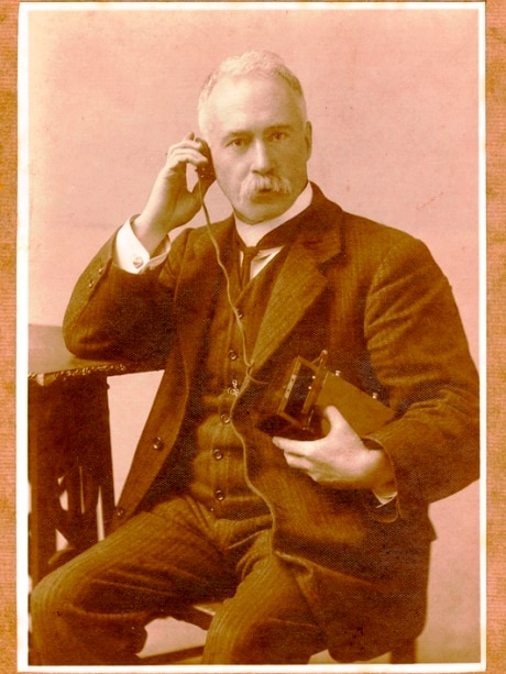 Black and white phone of man holding old radio