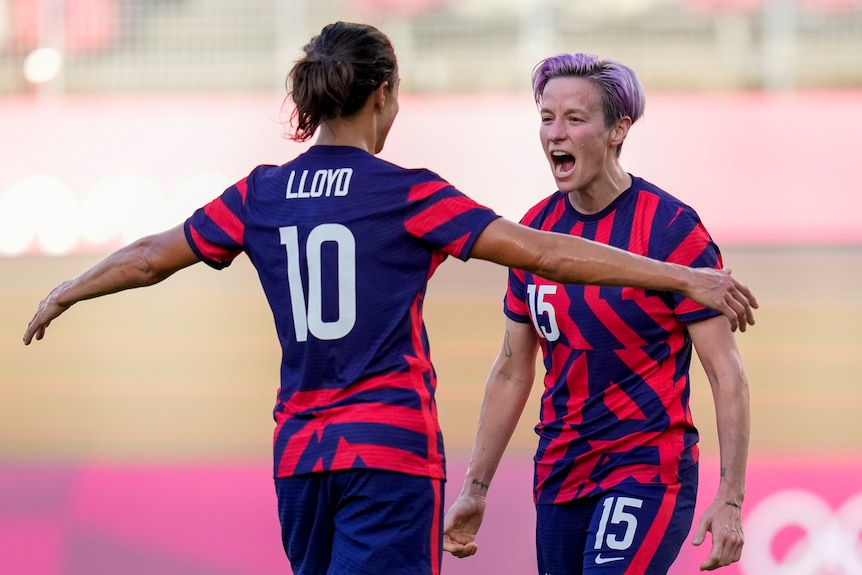 Two women celebrate during a football match at the Olympics.