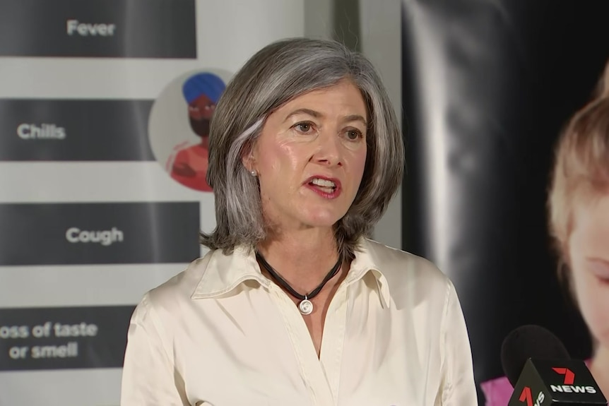 A woman with grey hair wearing a cream shirt