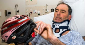 Peter Gee shows the helmet which saved his life from his hospital bed in tasmania