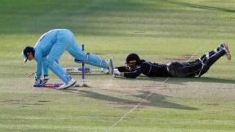 A batsman crashes to the pitch on his belly, bat outstretched, while a wicketkeeper retrieves the bales