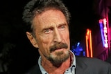 John McAfee in a suit looking right of screen with neon signs in the background