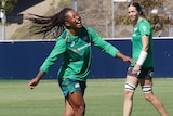 Young lady in green long sleeve shirt laughing while walking on a rugby field.