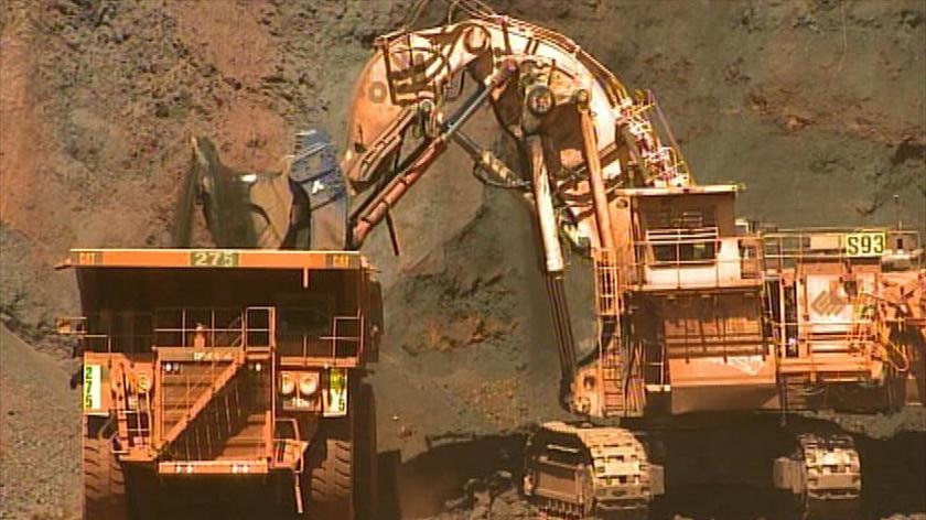 Iron ore is loaded into a large dump truck.