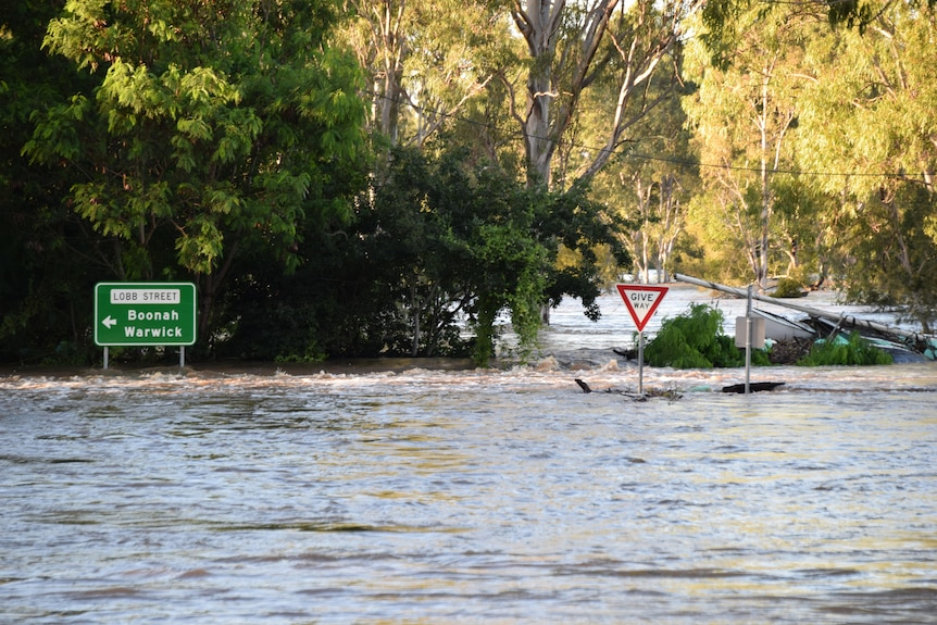 Street signs peak above the floodwater.