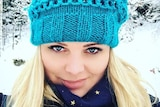A photo of a young blonde-haired woman wearing a blue beanie in a snowy location.