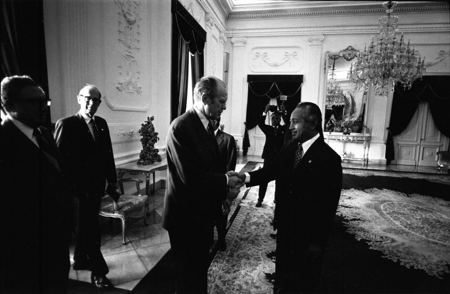 A black and white photo shows several men in a formal room, two of them shaking hands
