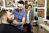Nathan Meers trims a customer's beard at the Happy Sailors barber shop.