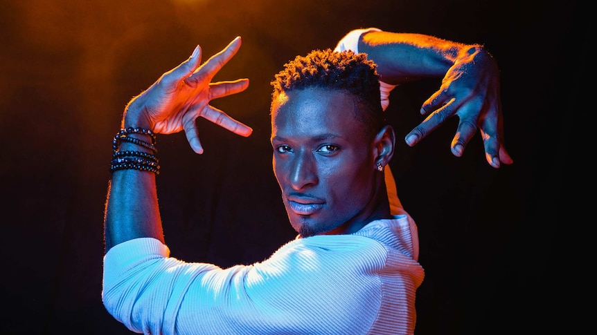 A dramatic colour close-up photo of Dashaun Wesley in a dance pose in front of dark background.