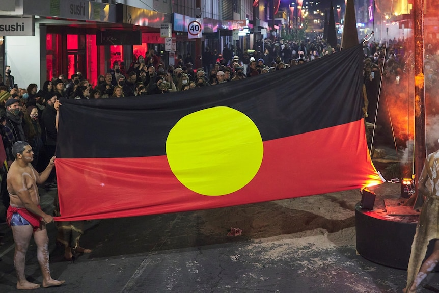 At night in a Hobart street, a young Aboriginal man holds up a Aboriginal flag, a large crowd of people gather behind the flag