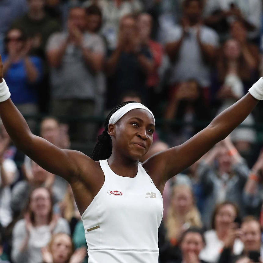 A girl on a tennis court smiling with her arms outstretched
