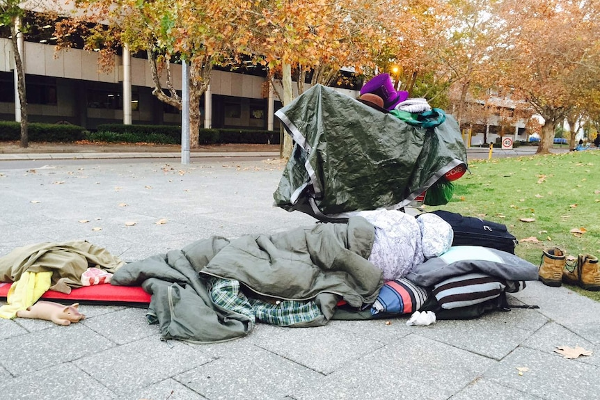 A homeless man sleeps on the street in Perth,