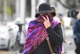 A woman covering her face with a scarf