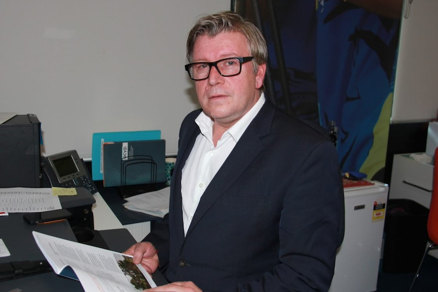 A man in glasses at an office desk.