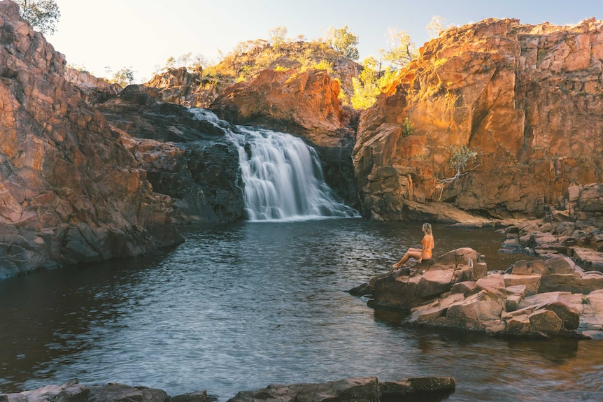 A woman in swimsuit sitting on a rock watching the waterfall at Edith Falls at sunrise