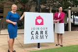 """Kate Jones and Annastacia Palaszczuk stand on either side of a sign that says """"join our care army'"""