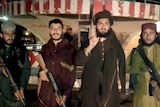 Taliban fighters stand with guns while record a video message