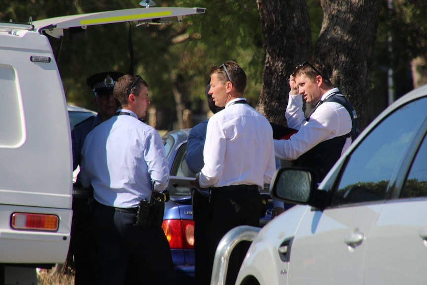 police stand between cars and near a tree after a shooting in Nollamara