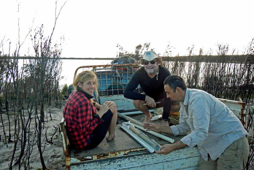 Researchers inspect core samples on Clarke Island