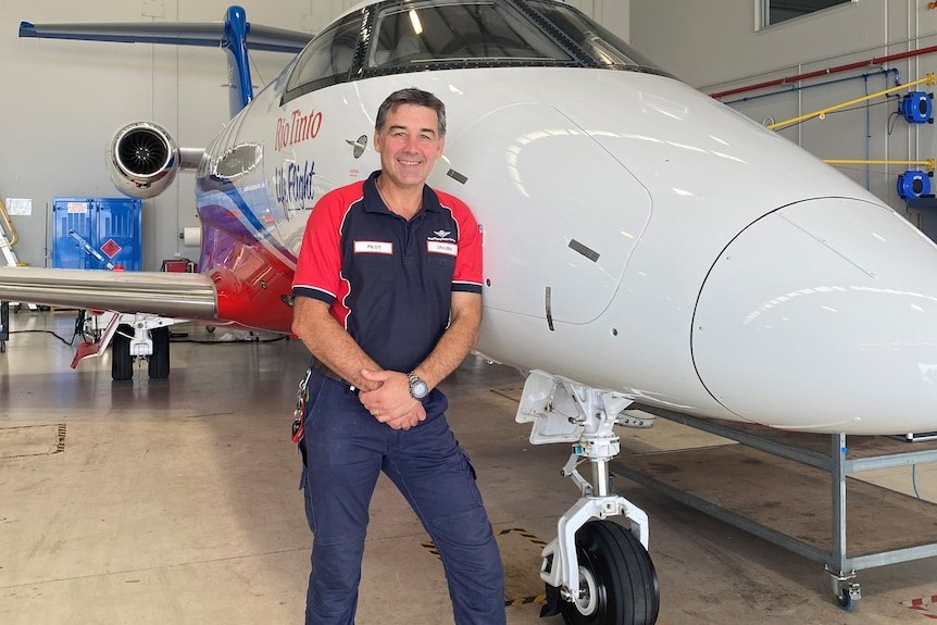 A man standing next to a jet airplane.