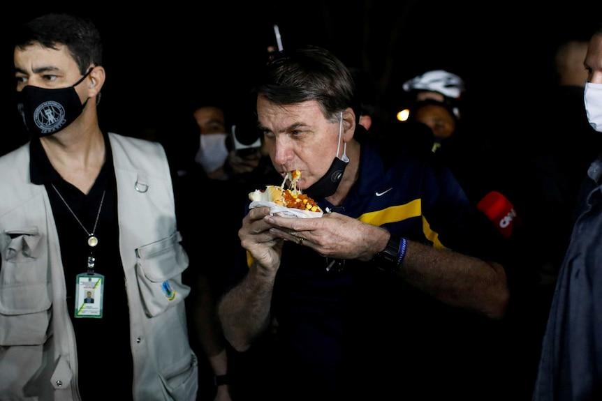 Jair Bolsonaro eats a hot dog while surrounded by body guards