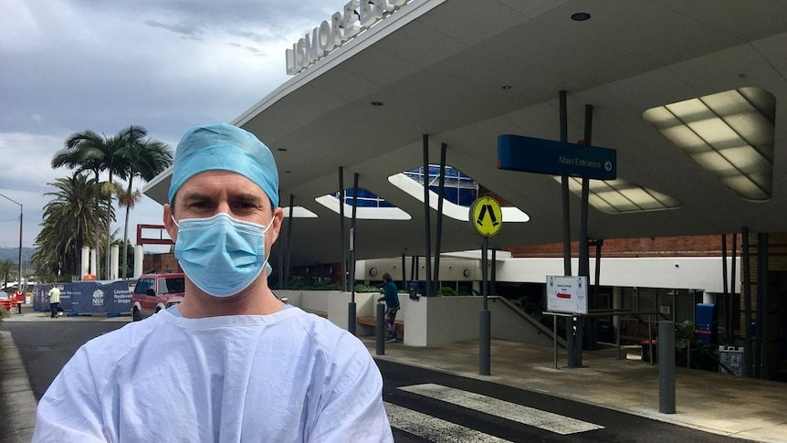 Male surgeon in pale blue scrubs, white apron, blue face mask and blue cap in front of hospital