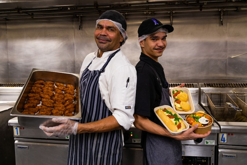 An older and younger man stand back to back, smiling, each holding trays of food.