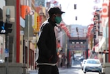 A man walking with a mask in Melbourne in early September 2020 with Chinatown in the background.