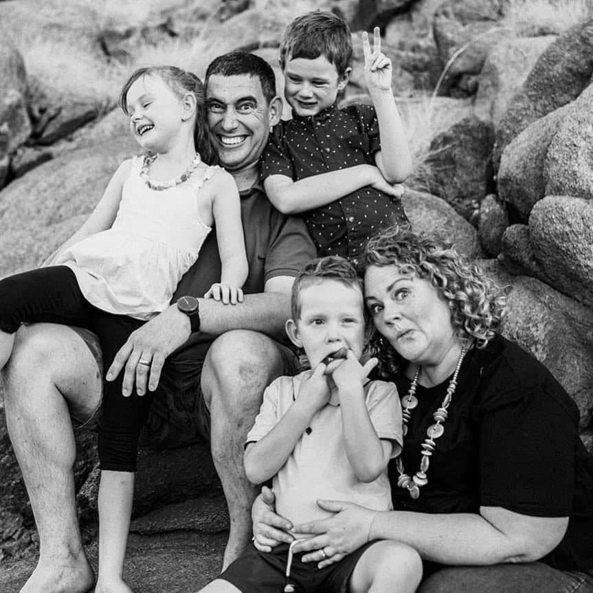 A black and white professional photo of a family making silly faces