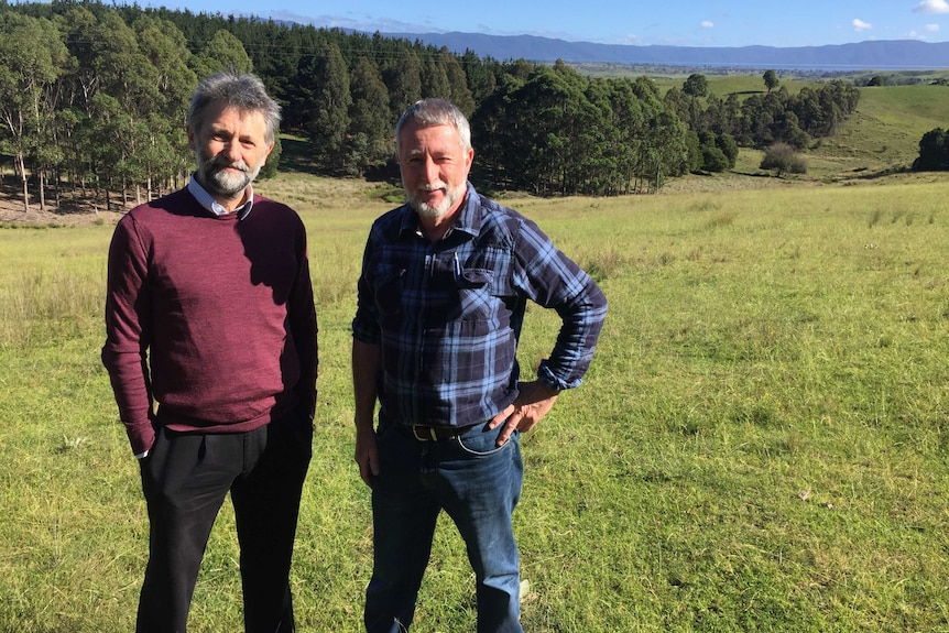 Phil Banks and John Coman standing in front of tree plantings on their farm