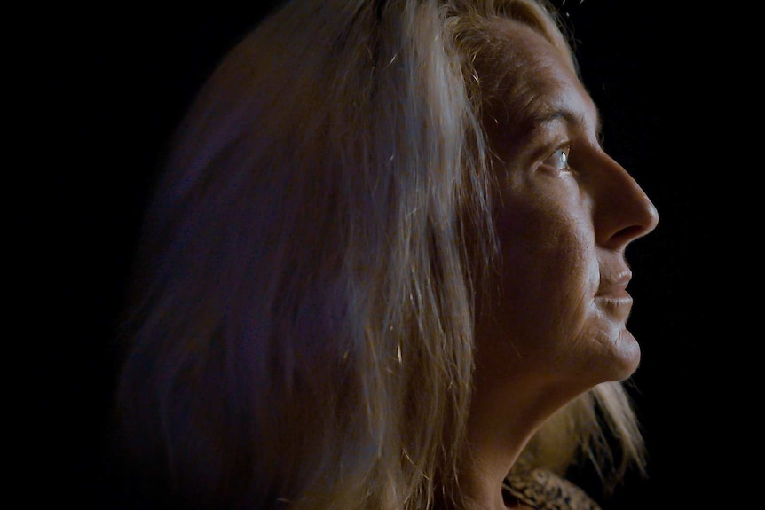 Nicola Gobbo in profile, half her face obscured by shadow.